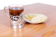 Thé chaud dans une rétro glace sur la table Photographie stock
