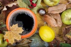 Thé chaud dans une tasse orange sur les feuilles sèches Photos libres de droits