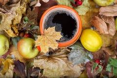 Thé chaud dans une tasse orange sur les feuilles sèches Photo stock