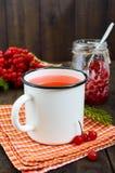 Thé chaud de baie dans une tasse blanche sur un fond en bois foncé Vue verticale Thé avec le viburnum Images stock