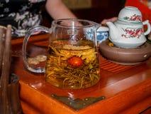Thé chinois de fleur à la théière en verre transparente image libre de droits