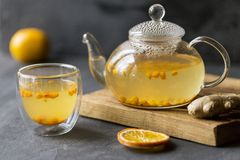 Thé d'épine de mâle de mer dans la théière en verre avec la tasse, l'orange et le gingembre en verre près de sur le fond noir photographie stock libre de droits