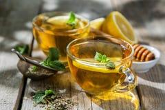Thé d'été - tasses de thé sur le fond en bois rustique avec des nuances de feuilles - jardin Photographie stock libre de droits