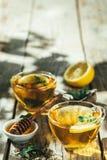 Thé d'été - tasses de thé sur le fond en bois rustique avec des nuances de feuilles - jardin Image stock