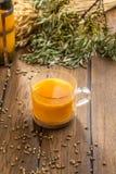 Thé d'argousier dans des transitoires de tasse et de blé sur la table en bois photographie stock