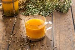 Thé d'argousier dans des transitoires de tasse et de blé sur la table en bois photographie stock libre de droits