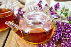 Thé d'origan dans la théière en verre avec la serviette Photo stock