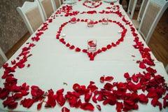 Thé d'un rouge ardent de ketmie dans une tasse en verre sur une table en bois parmi les pétales de rose et la crème anglaise sèch Images libres de droits