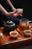 Thé dans des tasses, la cruche en verre et la théière, main tenant la tasse Photographie stock libre de droits