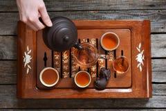 Thé dans des tasses, la cruche en verre et le thé se renversant de main humaine Images stock