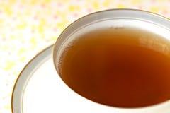 Thé dans la cuvette avec la soucoupe Photo stock