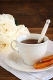 Thé dans la tasse élégante de porcelaine, oranges glacées Photo libre de droits