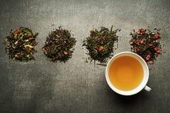 Thé dans la tasse avec la collection sèche de thés et d'herbes Photographie stock