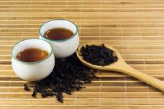 Thé dans la tasse avec la feuille de thé Images stock