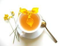 Thé dans la tasse blanche avec les fleurs et la main jaunes photographie stock libre de droits
