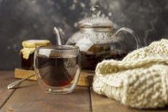 Thé dans la tasse en verre avec la théière et la couverture tricotée près, avec la confiture dans le pot au fond en bois, avec la photo libre de droits