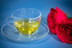 Thé dans les roses rouges en verre et belles Photographie stock libre de droits