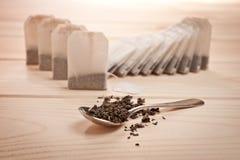 Thé dans les sacs et thé lâche dans une cuillère sur une surface en bois images libres de droits