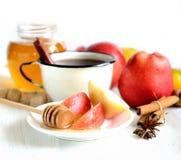 Thé dans un anis de tasse, de cannelle, de pommes, de miel et d'étoile en métal sur un fond blanc Image libre de droits