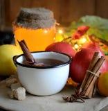 Thé dans un anis de tasse, de cannelle, de pommes, de miel et d'étoile en métal sur un fond foncé Photos stock