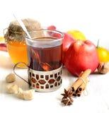 Thé dans un verre avec un anis de cuillère, de cannelle, de pommes, de miel et d'étoile sur un fond blanc Photo stock