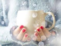 Thé dans une cuvette Neige en baisse Une fille tenant une tasse de thé Photos libres de droits
