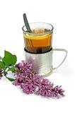 Thé dans une glace avec le lilas Image stock