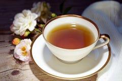 Thé dans une tasse blanche de porcelaine avec une jante d'or et une décoration rose Photos stock