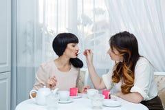 Thé de boissons d'amies avec le gâteau Photographie stock