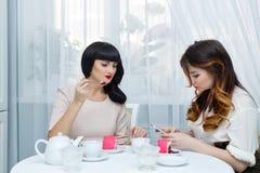 Thé de boissons d'amies avec le gâteau Réception de thé Photographie stock libre de droits