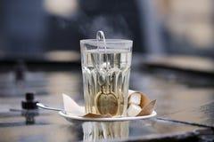 Thé de brassage dans une tasse d'eau bouillante Images libres de droits