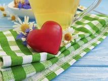 Thé de camomille, biscuit de fines herbes de bleuet, coeur romantique sur un fond en bois Photos libres de droits