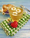 Thé de camomille, biscuit de fines herbes de vintage de bleuet, coeur romantique sur un fond en bois Photos libres de droits