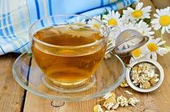 Thé de camomille de fines herbes avec un tamis et une tasse en verre Photographie stock libre de droits
