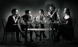 Thé de cinq filles de beauté buvant à la table Images stock