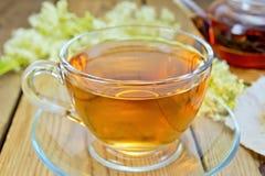 Thé de meadowsweet dans la tasse et la théière en verre Photographie stock