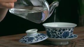 Thé de processus de brassage, cérémonie de thé, tasse de thé noir fraîchement brassé Service à thé asiatique sur le tapis en bamb banque de vidéos