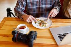 Thé de repos et mangeant de jeune homme et potable dans le café images stock