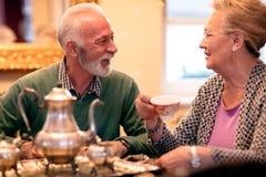 Thé de sourire et potable de beaux couples supérieurs à la maison de repos Photo libre de droits