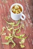 Thé de tilleul dans une tasse sur un fond en bois Image libre de droits
