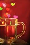 Thé de tradition dans une tasse de verre avec la baisse de bokeh de lumière de coeur Photos libres de droits