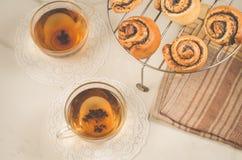 thé deux et petit pain avec le pavot sur un trellis pour le thé de cuisson/deux verres et petit pain en verre avec le pavot sur u images libres de droits