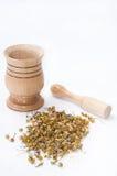 Thé en bois de mortier et de camomille sur un fond blanc photo libre de droits