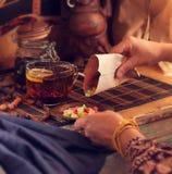 Thé et bonbons La femme met la sucrerie sur un plat images stock