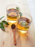 Thé et feuilles de thé sur la table en bois Photo stock