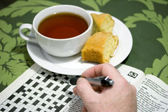 Thé et jeu de mots croisé de matin Photographie stock