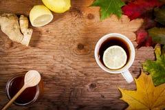 Thé et miel sur la table avec des feuilles d'automne Image libre de droits