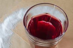 Thé et sachet à thé rouges chauds en verre, sucre renversé autour sur le papier brun lumineux image libre de droits