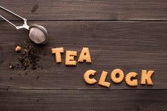 Thé et une inscription de biscuit sur un fond en bois photographie stock