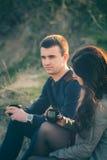 Thé extérieur de jeunes couples affectueux ensemble et potable heureux Un type avec une fille sur le lac au coucher du soleil boi image stock